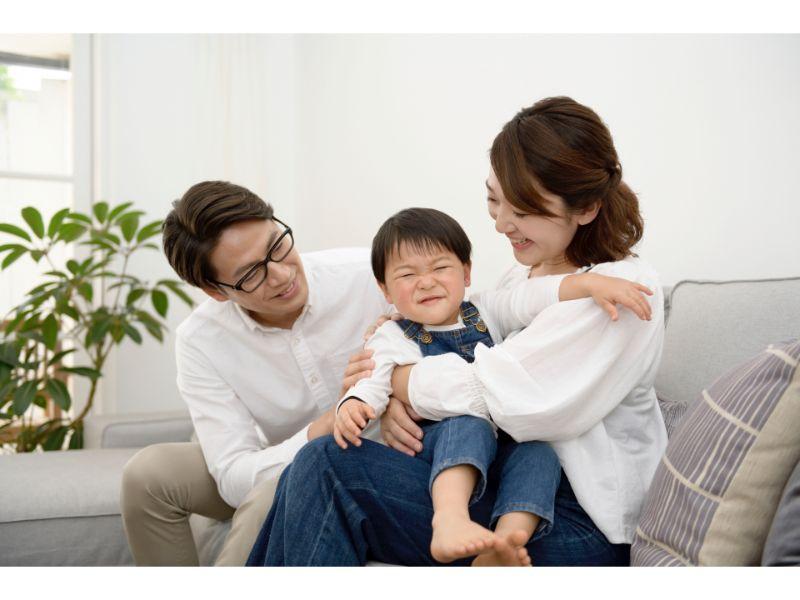 両親と子供が笑っている写真