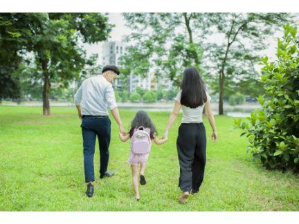 間に子供を挟んで手を繋ぐ家族の写真