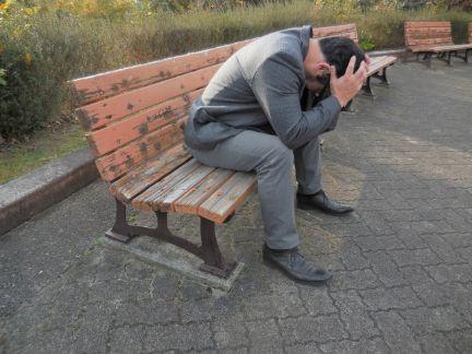 ベンチで頭を抱える男性の写真