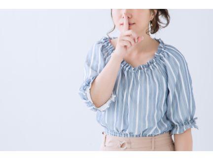 女性がシーと口元に人差し指を当てる写真