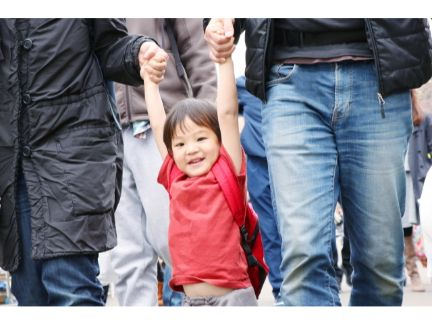 両親の間で手を繋ぐ子供の写真