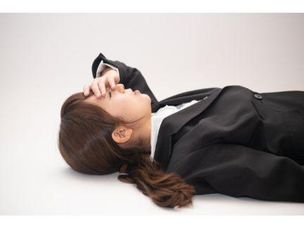 疲れて横になる女性の写真