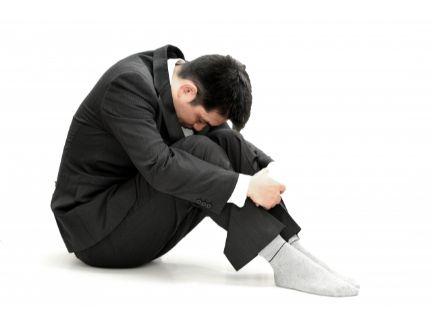 膝を抱えて落ち込む男性の写真
