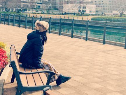 ベンチに座って物思いにふける女性の写真