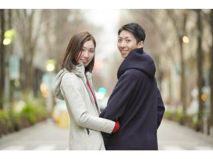 腕を組んで振り向く仲良しカップルの写真