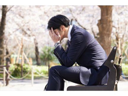 ベンチで悩む男性の写真