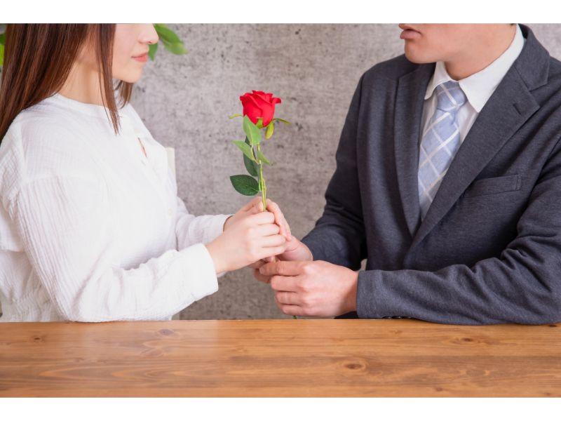 女性に一輪のバラを渡す男性の写真