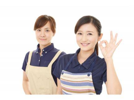 OKサインをする女性店員の写真