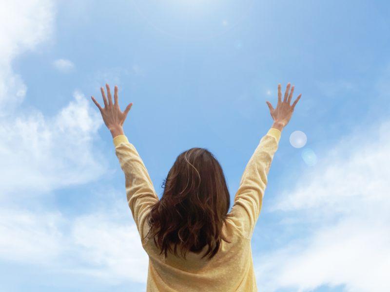 大空に両手を広げる女性の後ろ姿