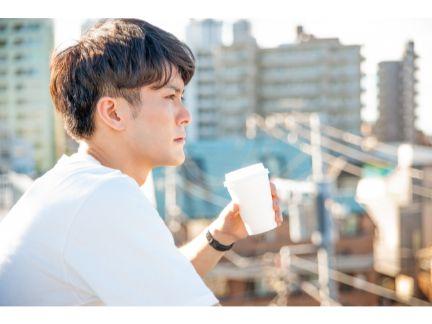 屋上で遠くを見つめる男性の写真
