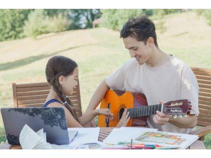 子供にギターを弾く男性の写真