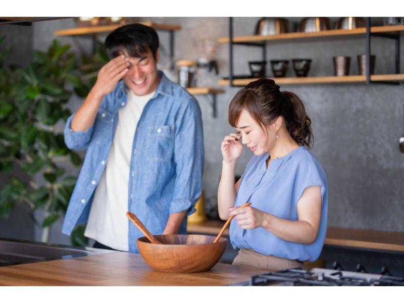 料理をしながら泣く女性と困る男性の写真