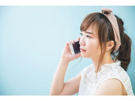 迷惑そうな顔で電話する女性の写真