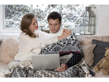 PCを見ている男性に抱きつく女性の写真