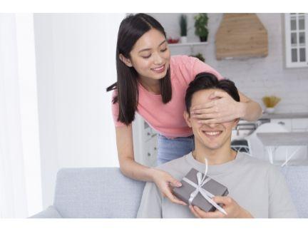 男性に目隠しをしてプレゼントを渡す女性の写真
