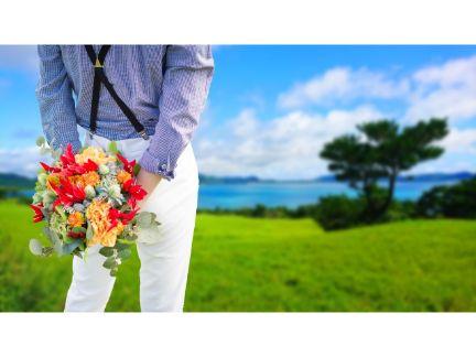 後ろに花束を持った男性の写真