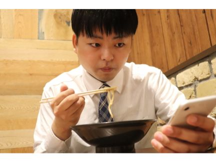 スマホを見ながらラーメンを食べる男性の写真