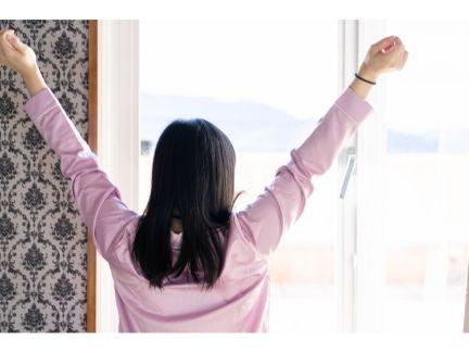 カーテンを開けて伸びをする女性の写真