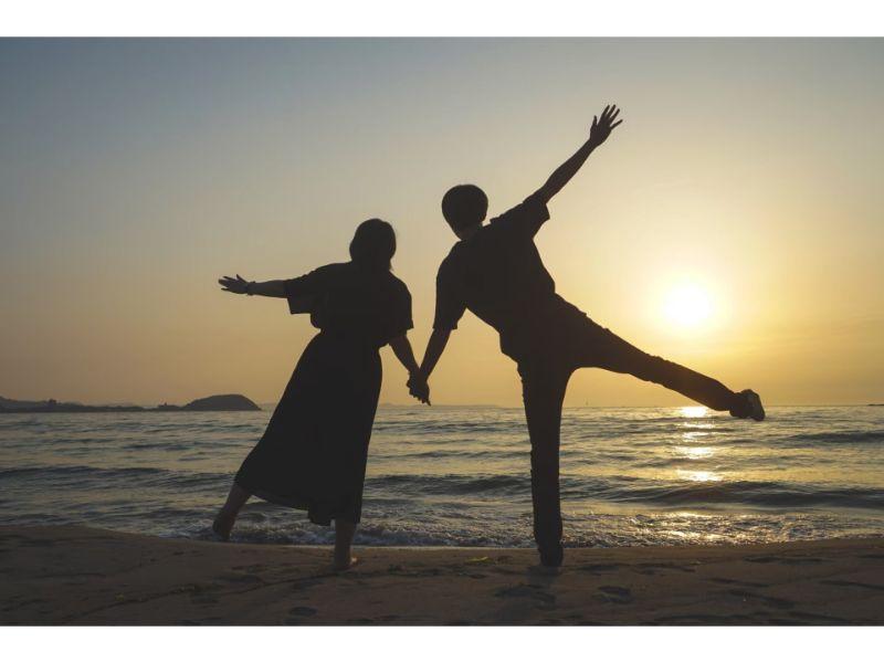 男女が海に向かって手を広げているシルエット