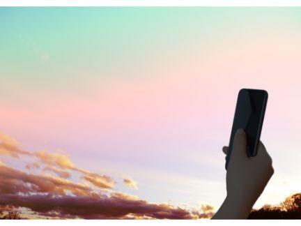 夕空にスマホをかざす写真