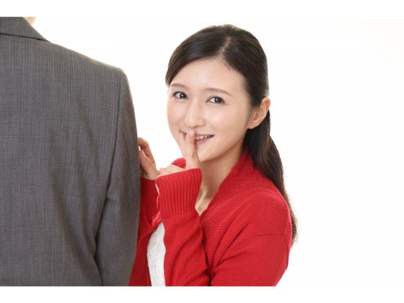 後ろ向きの男性とシーと指を立てて寄り添う女性の写真