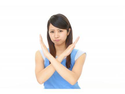 嫌そうな顔で腕を×にする女性の写真