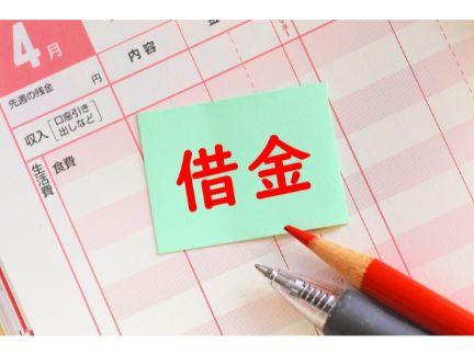 家計簿の上に「借金」と書かれた付箋が貼ってある写真
