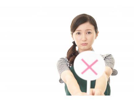 バツの札を持つ女性の写真