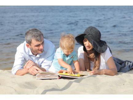 砂浜の上で絵本を読む家族の写真