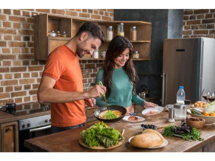 仲良く料理するカップルの写真
