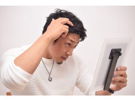 髪形を気にする男性の写真