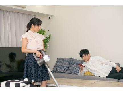 掃除している女性が何もしない男性を怒った表情で見ている写真