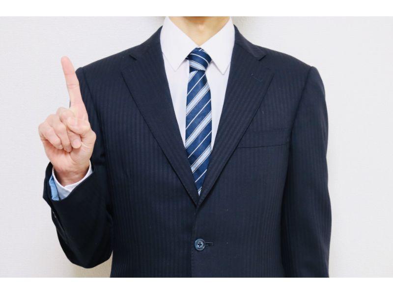 人差し指を立てた男性の写真