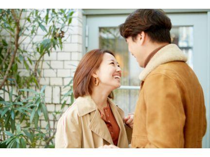笑顔で向かい合うカップルの写真
