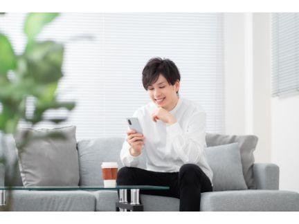 スマホを見ながら笑う男性の写真
